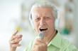 Senior man in headphones singing