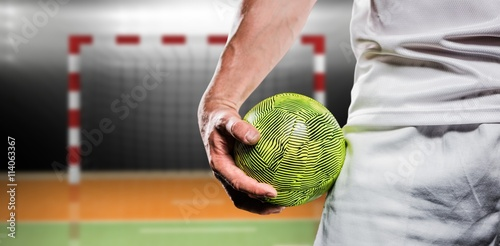 Composite image of sportsman holding a ball