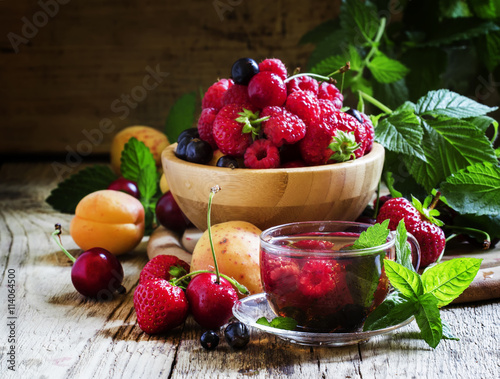 Summer fruit tea with mint in a glass cup, fresh fruit and berri