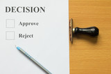 Decision paper with blue pen and rubber stamp