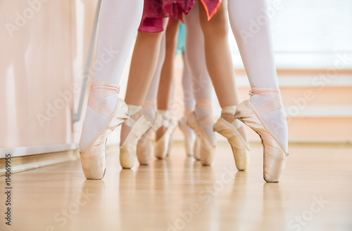 Legs of young ballerinas standing on pointe in row, ballet dancing class  © Andrey Bandurenko