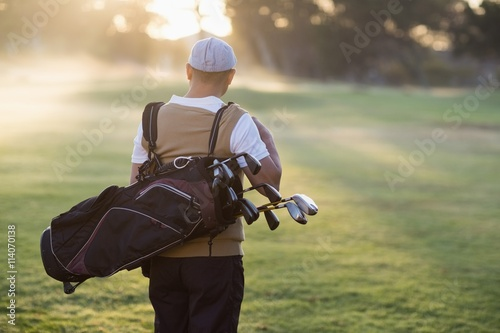 Rear view of man carrying golf bag