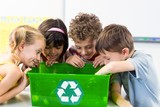 Children looking at plastic bottles in recycling box - 114070912