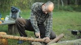 Man sawing a small tree camp saw. Near lit a fire and lay the tourist stuff