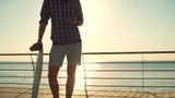 handsome male holding longboard and using smartphone slow motion