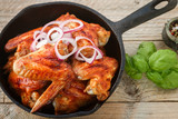 Delicious fried chicken wings with spices in a frying pan on the table
