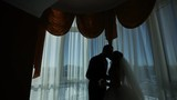 happy luxury bride and groom standing at window light in rich room