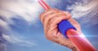 Composite image of close-up of hand holding javelin