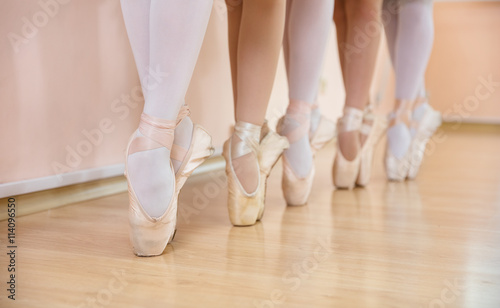 Legs of young ballerinas standing on pointe in row, ballet dancing class  © Andrey Bandurenko