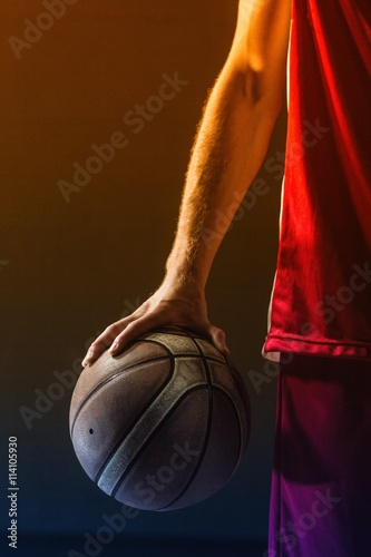 Close up on basketball held by basketball player Poster