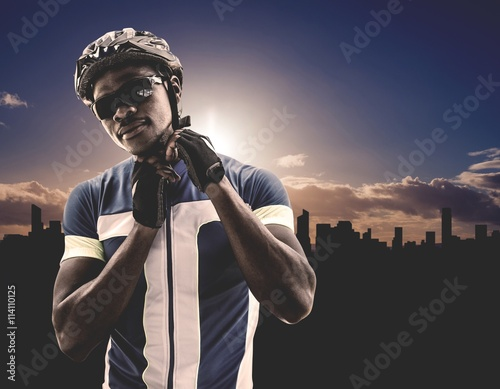 Poster Composite image of athletic man putting his cycling helmet
