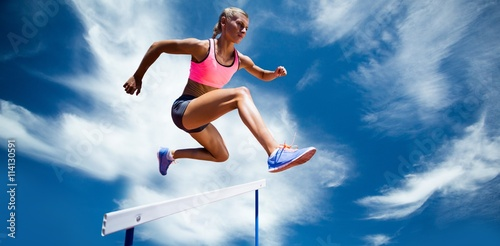 Composite image of sporty woman jumping a hurdle - 114130591