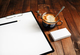 Close-up of blank paperwork template. Blank stationery set on vintage wooden table background. Paper, blank letterhead, coffee cup and pencil. Mock-up for design portfolios. Top view.