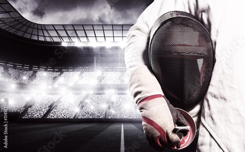 Fototapeta Composite image of mid-section of man standing with fencing mask