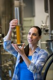 Female brewer holding hydrometer cylinder