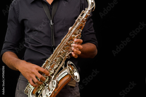 Poster Nice hands touching a silver saxophone, black background