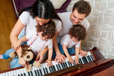 Parents with daughters twins study music at the piano. Top view
