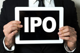 Business man holding tablet with the text: IPO