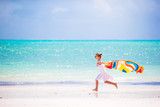 Fototapety Little girl have fun with beach towel during tropical vacation