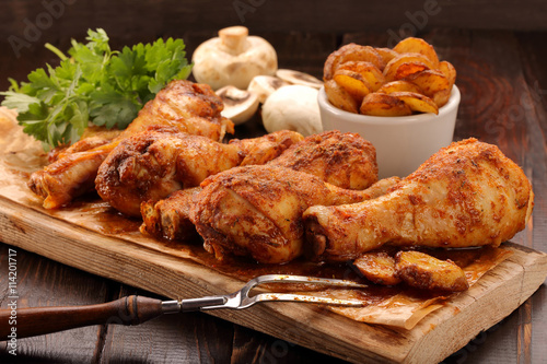 obraz PCV Roasted chicken legs with potato chips and vegetables