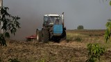 Tractor plowing a field in country side. 4K stock footage clip.