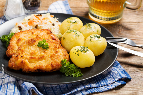 obraz PCV Fried pork chop in breadcrumbs, served with boiled potatoes and