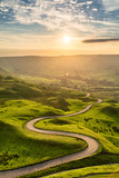 Fototapety Winding country road leading to Edale in the English Peak District with beautiful golden light shining through valley.