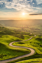 Winding country road leading to Edale in the English Peak District with beautiful golden light shining through valley. © danielkay