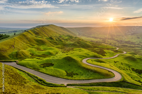 Fotobehang Zomer Long winding country road leading through rural countryside in the English Peak District with beautiful evening sunlight.