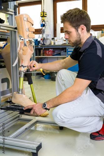 Homme travaillant sur l'assemblage de la jambe prothétique. Poster