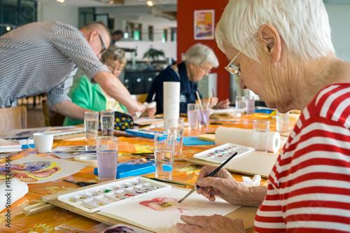 Leinwanddruck Bild Woman working on watercolor painting.
