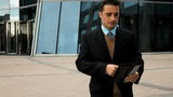 Young successful businessman black suit goes to work and uses black tablet PC for Internet serfing and smile. Modern glass business centre bg. Teal orange style. slow motion 250 fps portrait middle