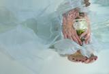 Brides hands and feet, flowers, underwater wedding in pool