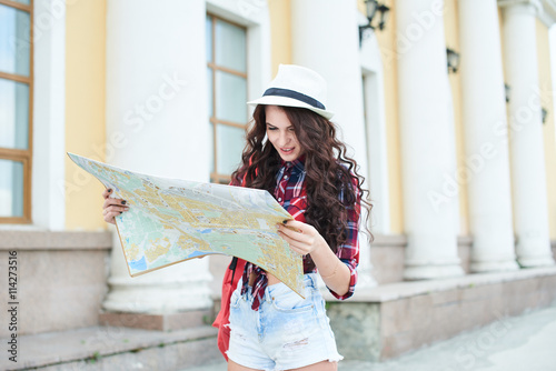 Tourist girl in a hat holding a map and looking at her against the building with columns