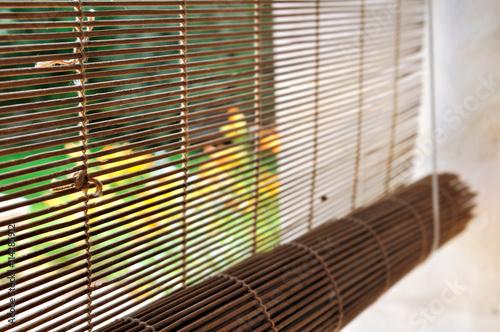 store en bambou sur une fenêtre donnant sur un jardin
