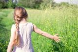 Little dreamy girl walks in the field
