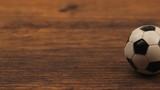 Miniature plastic soccer ball on wooden table, dolly slider camera motion