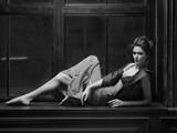 Tall model lying on the windowsill in dark midi leather jacket