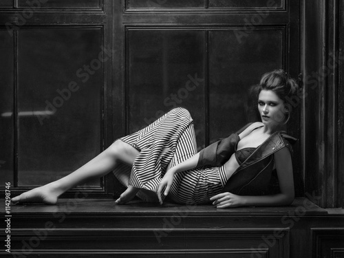 Tall model lying on the windowsill in dark midi leather jacket