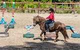 little girl is riding a horse - 114309549