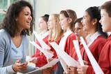 Fototapety Children In School Choir Being Encouraged By Teacher
