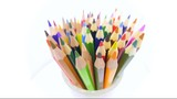 Color pencils turning on a white background. Close up.