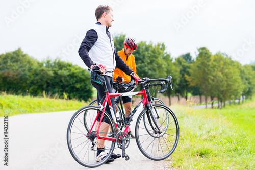 Zwei Sport Radfahrer, abgestiegen, machen eine Pause Poster