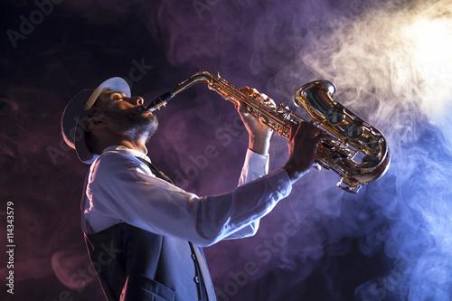 Saxofonista sobre escenario con humo Poster