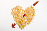 Top view of heart with an arrow made of pasta in two types and two colours, on the white background with copy space