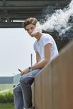 Junger Mann in T-Shirt und Jeans sitzt e-Zigarette rauchend auf einer rostigen Absperrung unter einer Stahlbrücke und bläst lässig eine weiße Dampfwolke.