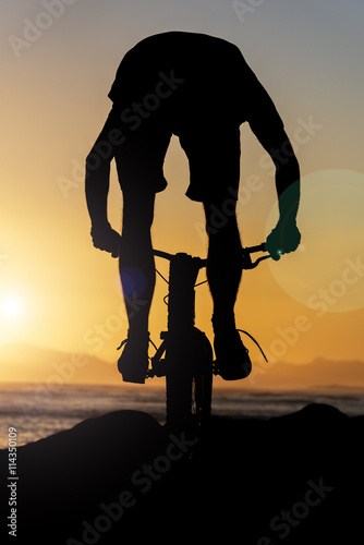obraz PCV CYCLIST RIDING OVER ROACKS INTO A SOUTH AFRICAN SUNSET