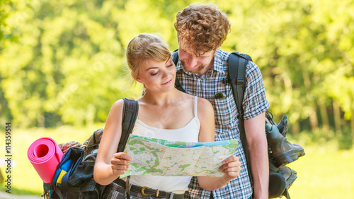fototapeta na ścianę Hiking backpacking couple reading map on trip.