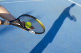 Artistic image, tennis player no face preparing to serve, shadow on blue tarmac
