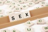 """La parola """"sesso"""" scritta in inglese con lettere stampate su tessere di legno."""